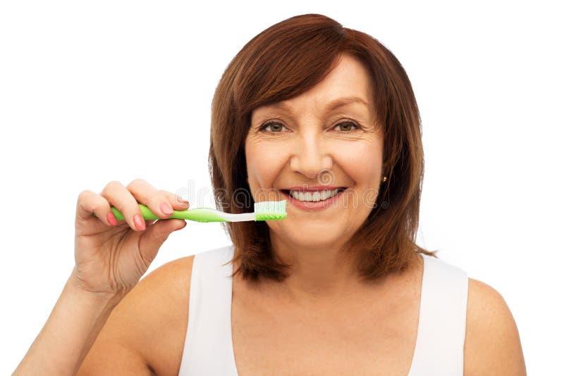 有刷她的牙的牙刷的资深妇女 免版税库存照片