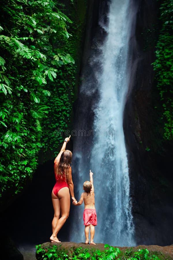 有儿子立场的母亲在瀑布下 库存照片