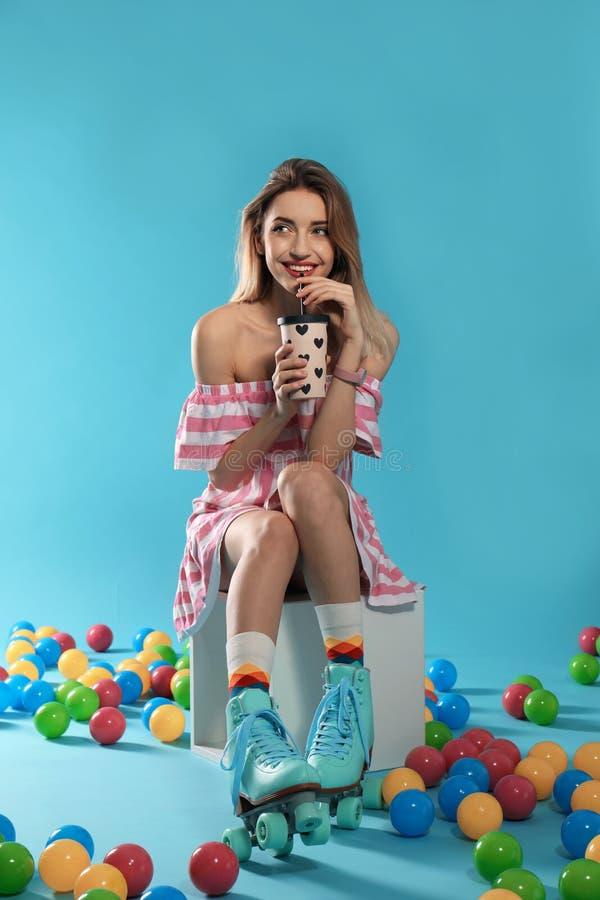有减速火箭的溜冰鞋和杯子的年轻女人饮料 库存图片