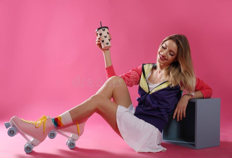 有减速火箭的溜冰鞋和杯子的年轻女人饮料 库存照片