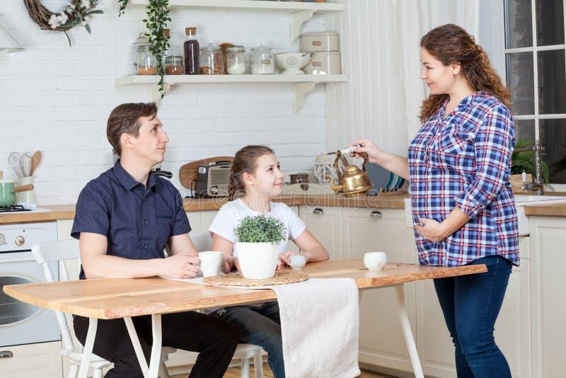 有准备早餐的茶壶的怀孕的妻子对丈夫和青少年的年龄女儿在厨房 图库摄影