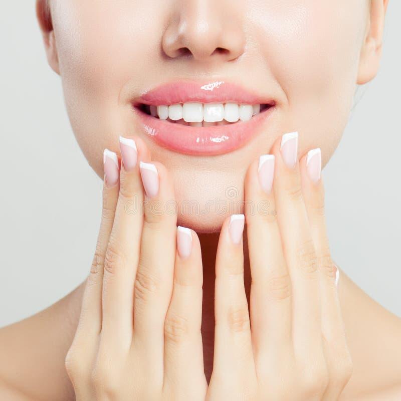 有光滑的桃红色构成的美丽的女性嘴唇和有法式修剪钉子的,特写镜头画象被修剪的手 库存照片