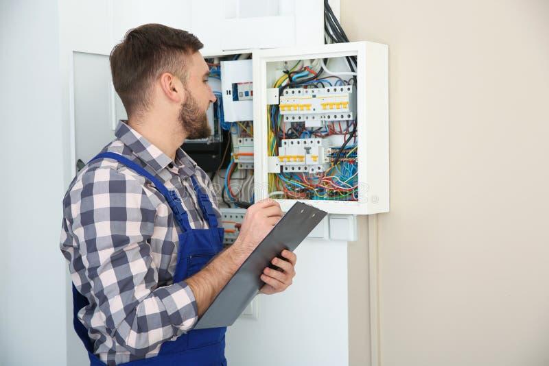 有剪贴板的男性电工在户内保险丝板附近 免版税库存图片