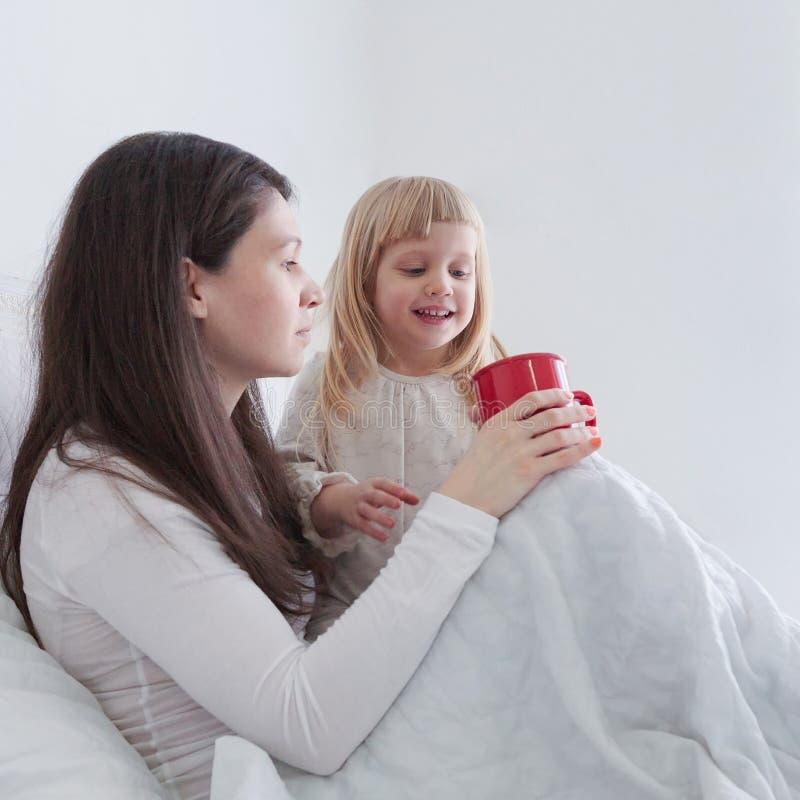 有喝一些茶的女儿的年轻母亲,当坐在床上在卧室时 库存照片