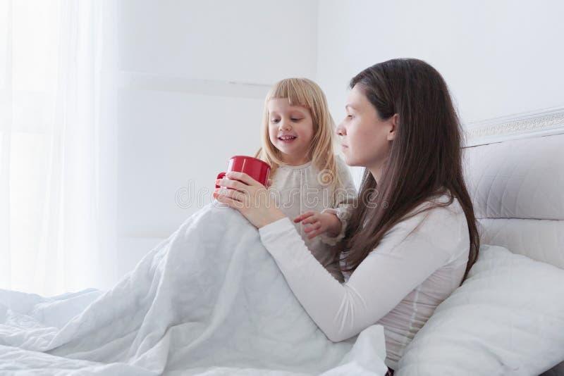 有喝一些茶的女儿的年轻母亲,当坐在床上在白色卧室时 免版税库存照片