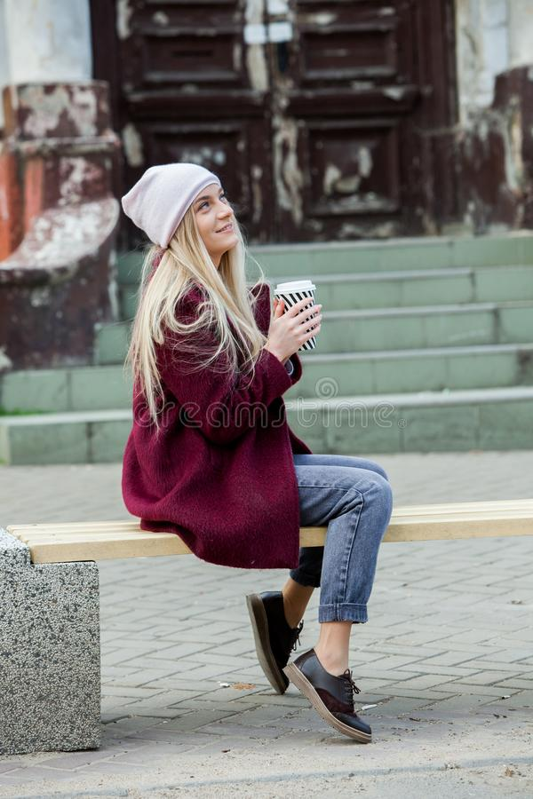 有咖啡的华美的年轻女人在城市街道的 背景中断咖啡新月形面包杯子甜点 咖啡去 时髦的在街道的行家女孩饮用的咖啡 库存图片