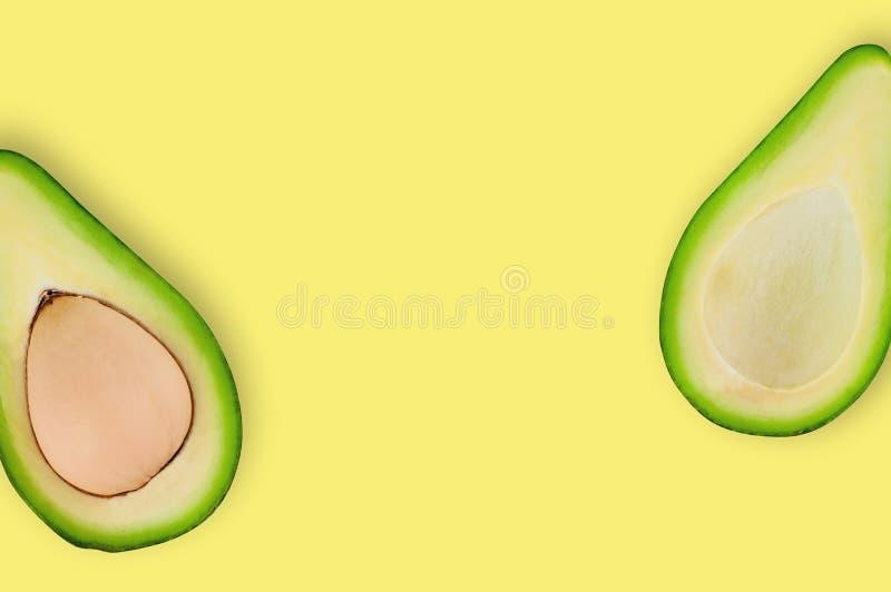 有和没有有机鲕梨仁的新一半在黄色桌上的在厨房或市场上 顶视图 烹调概念 免版税库存照片