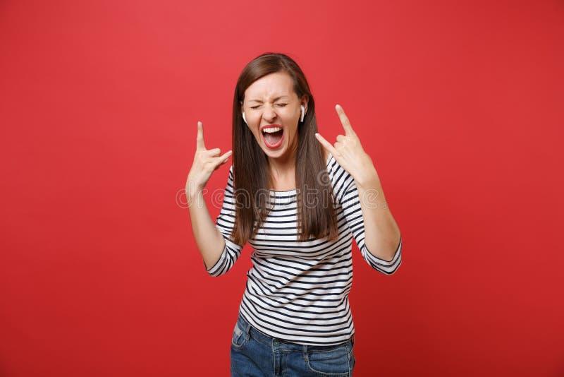 有描述重金属的岩石垫铁标志,听的音乐的无线耳机的尖叫的年轻女人隔绝在红色 免版税库存图片