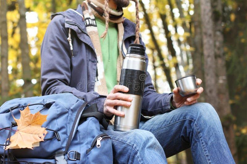 有杯子的人热的饮料-茶或咖啡和热水瓶在有背包的,枫叶秋天森林里坐 库存照片