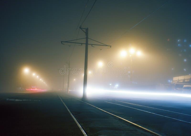 有杆的路与高压导线和电车轨道或者电车路轨,平衡在街道上的雾,与高压导线的杆 图库摄影