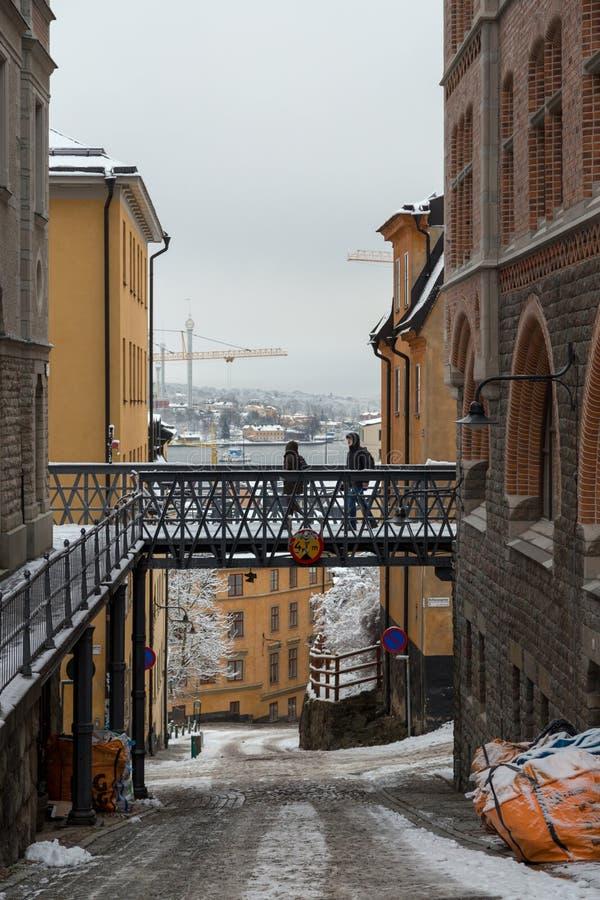 有桥梁的狭窄的空的街道有走在与雪,斯德哥尔摩瑞典的一天的turist的 免版税图库摄影