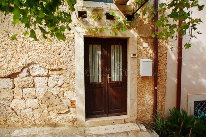 有棕色大门和夏天庭院容器的迷人的小家充满每年花 库存照片