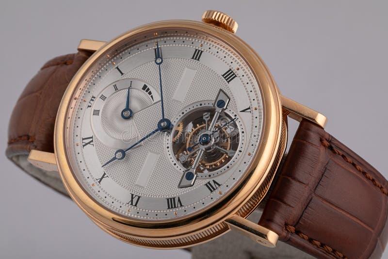 有棕色皮带的,白色拨号盘人的手表,在金黄身体,蓝色顺时针,秒表,数字隔绝在灰色背景 免版税图库摄影