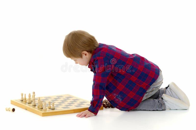 有棋枰的小男孩 库存照片