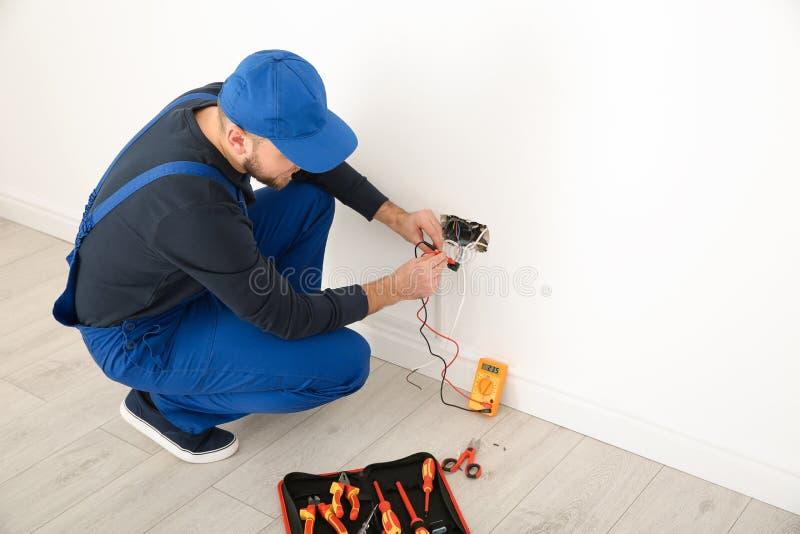 有检查电压的测试者的电工户内 库存图片