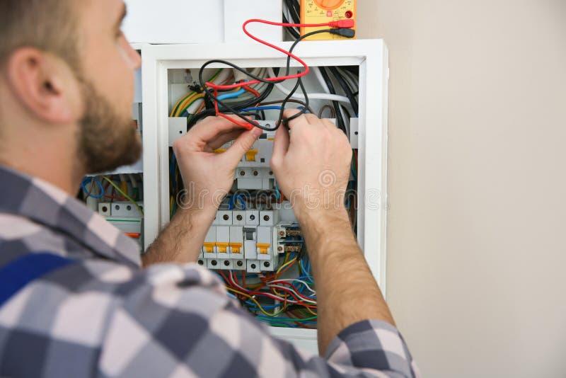 有检查电压的测试者的电工户内 免版税图库摄影