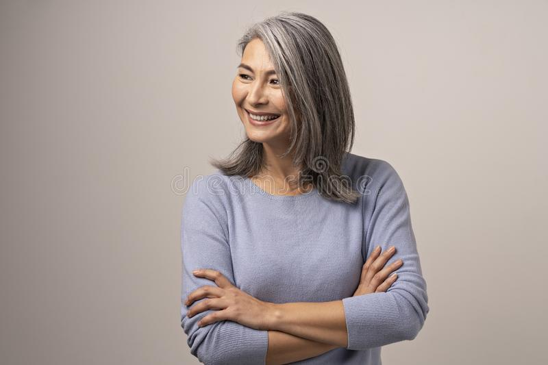 有横渡的胳膊的微笑的亚裔资深妇女 图库摄影