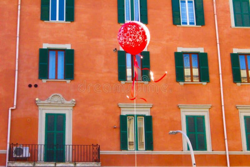 有橙色大厦的红色气球在背景 库存图片