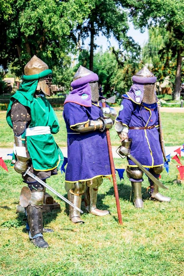 有武器的三位中世纪战士在fight_前 免版税库存照片