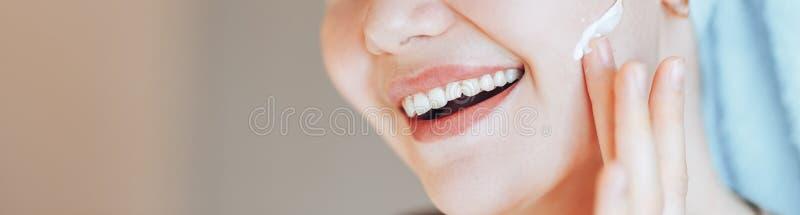 有毛巾的愉快的微笑的俏丽的美女女孩在头微笑的接触健康干净的软性以后润湿了水合的皮肤护理 库存照片