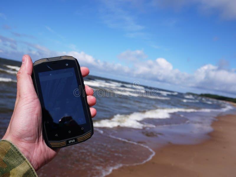 有水和尘土保护的智能手机 库存图片