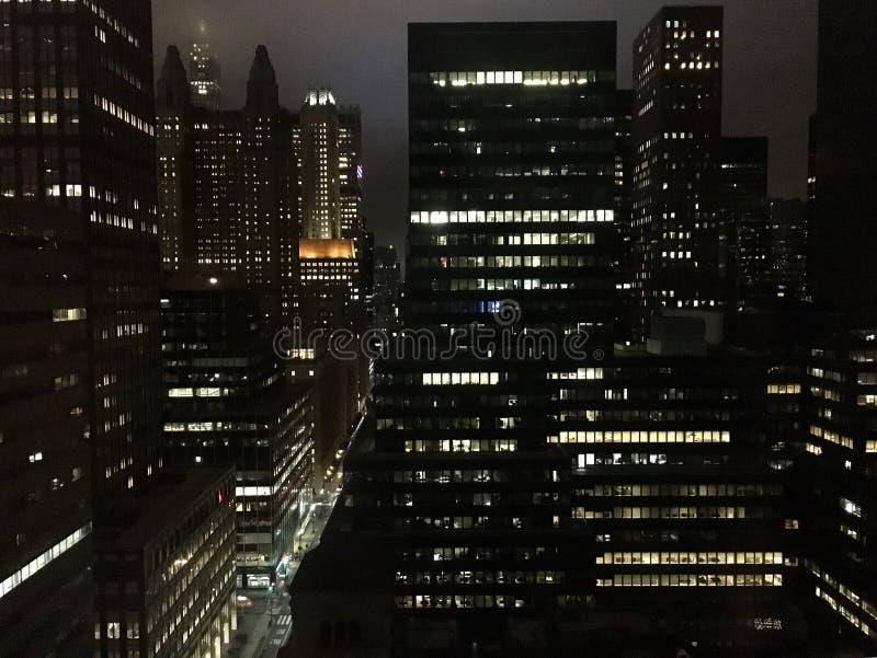 有汽车和高被点燃的摩天大楼小河的纽约街反对夜空 库存图片