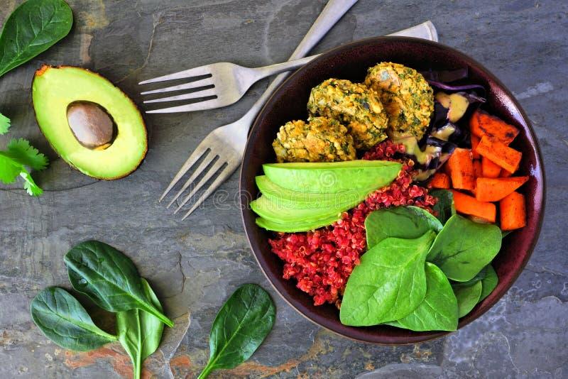 有沙拉三明治、甜菜奎奴亚藜、鲕梨和菜的健康素食主义者午餐碗在黑暗的石头 库存图片