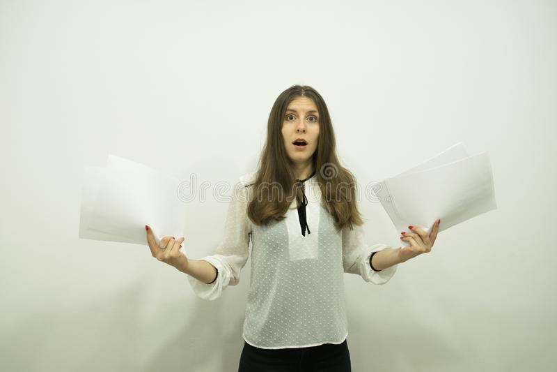 有流动的头发立场的女孩在框架的中心,拿着白色板料在她的手上和非常惊奇 免版税图库摄影