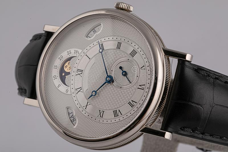 有测时器、秒表在皮带与白色拨号盘,黑在白色背景隔绝的数字和手的人的手表 库存照片