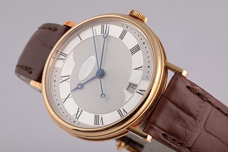 有测时器的人的手表,与白色拨号盘的皮革棕色皮带,黑在白色背景隔绝的数字和蓝色手 库存照片