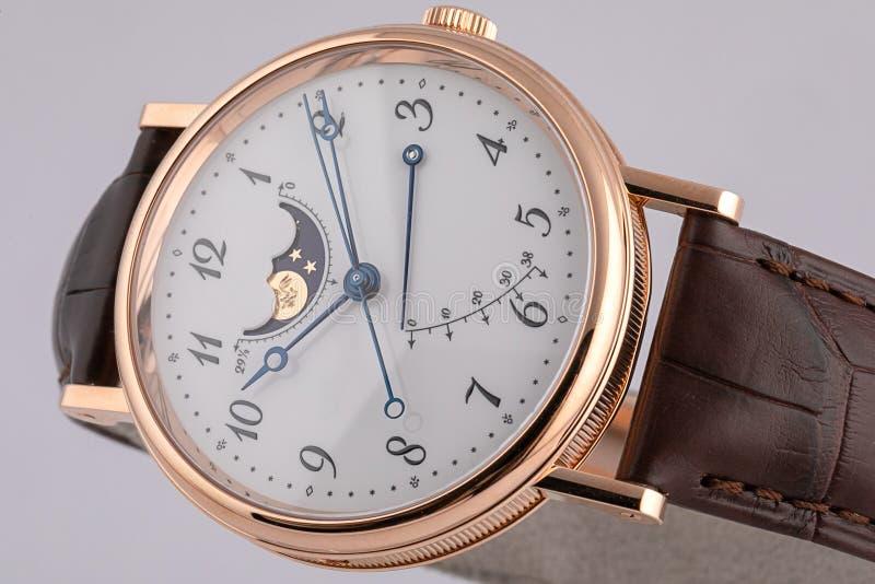 有测时器的,在皮革棕色皮带的秒表人的手表与白色拨号盘,黑数字隔绝在白色背景 库存照片