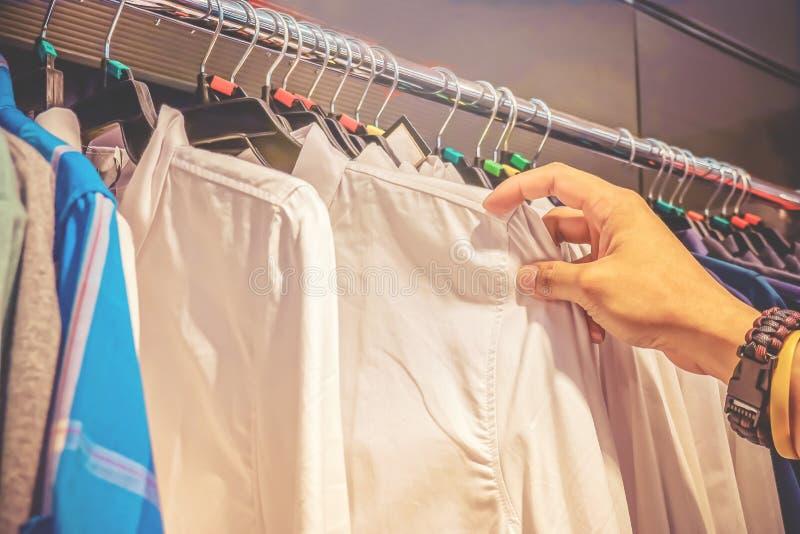 有挂衣架的机架在超级市场 男性手接触从很多衣裳的一些衬衣并且选择某一项目 免版税库存照片
