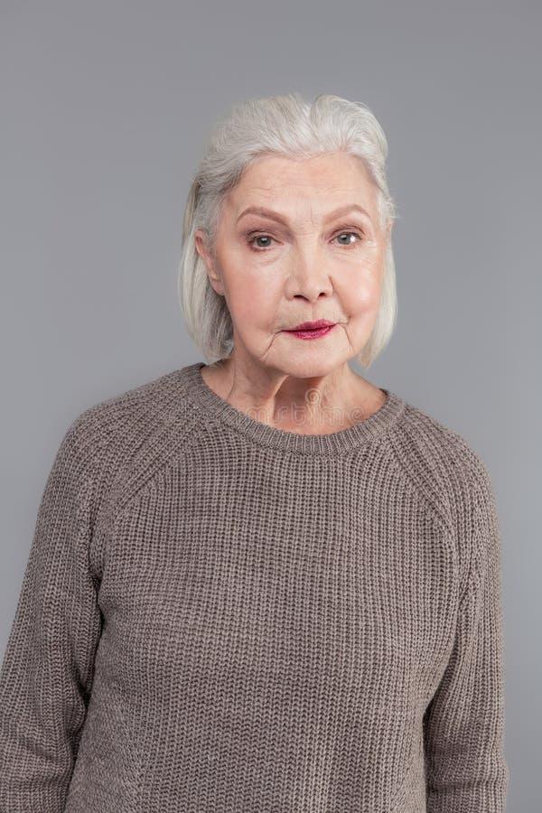 有有突然移动的理发的老妇人,黑暗的唇膏,当穿灰色毛线衣时 库存照片