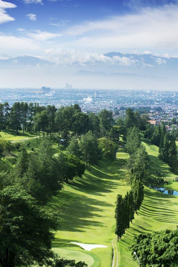 有有薄雾的万隆都市风景的绿色高尔夫球场 库存图片