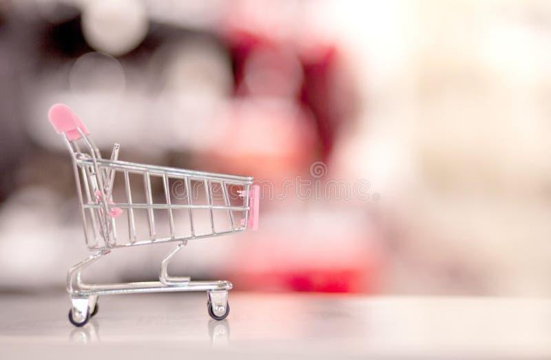 有抽象迷离超级市场廉价商店走道和产品架子内部defocused背景的空的购物车 免版税库存照片