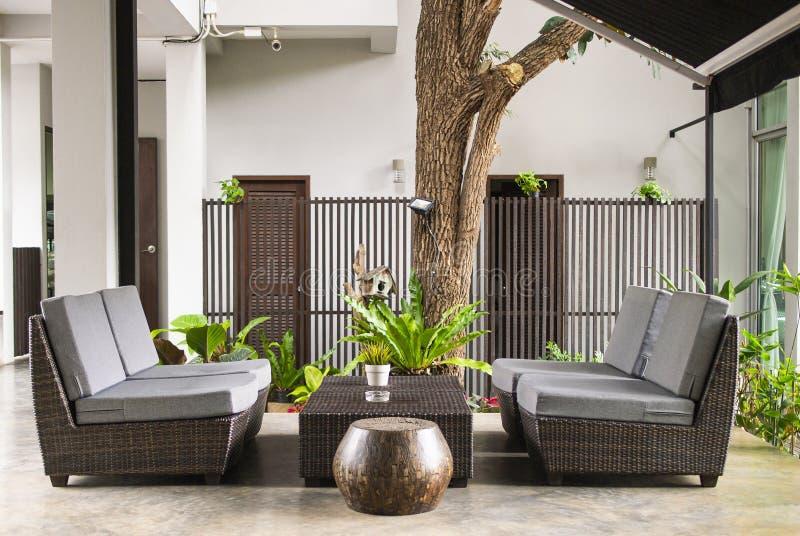 有枕头的柳条沙发和在庭院大阳台的桌身分由房子 免版税库存图片