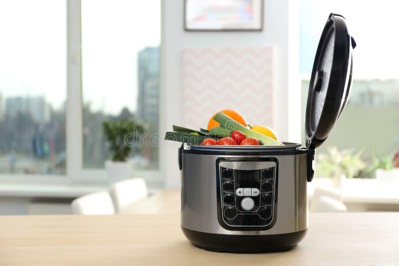 有成份的现代多烹饪器材在桌上在厨房里 免版税库存图片