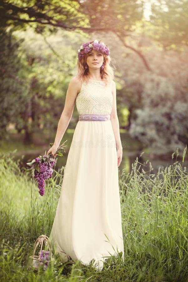 有户外花的美女在绿草背景在春天浪漫天 库存照片