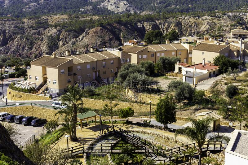 有房子、停车处和区域休息的和步行的西班牙村庄在山的脚,Fenistrat西班牙 免版税库存照片