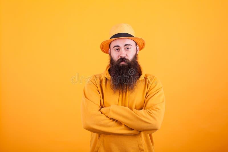 有戴在黄色背景的长的胡子的行家橙色帽子 库存图片