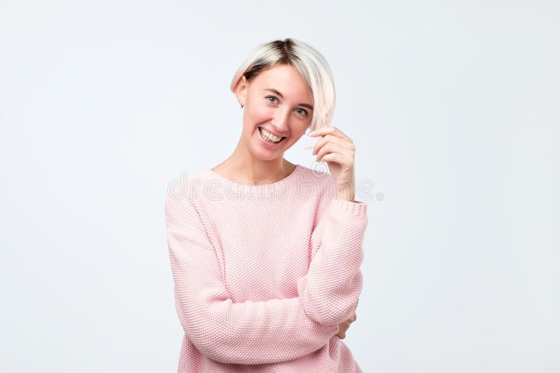 有是短的被染的头发的妇女非常高兴微笑与显示她完善的牙的开朗的笑 图库摄影