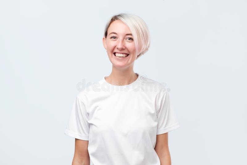 有是短的被染的头发的妇女非常高兴微笑与显示她完善的牙的开朗的笑 免版税库存照片
