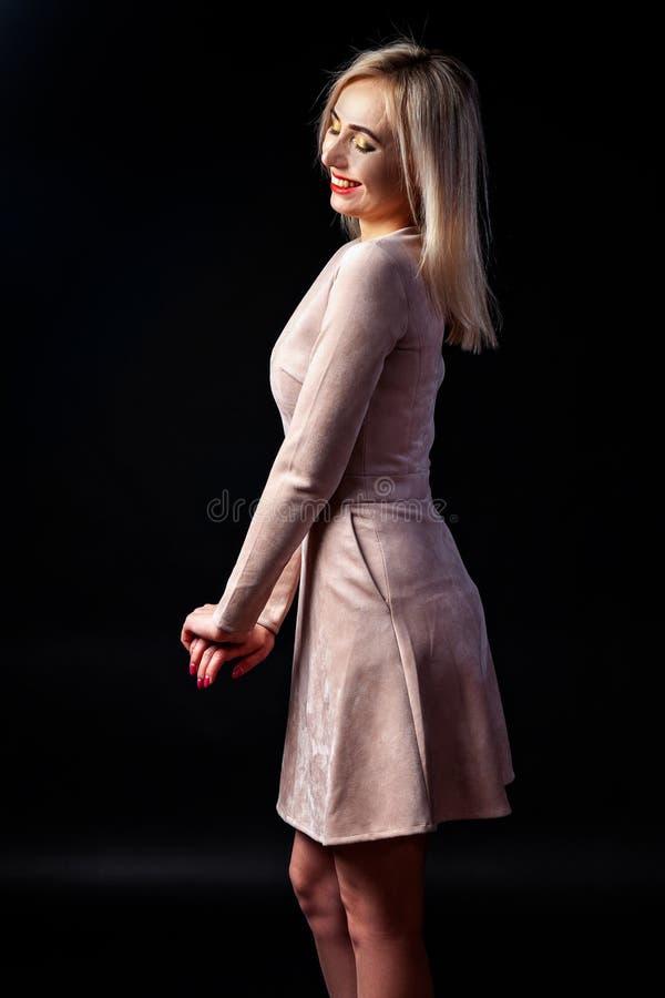 有明亮的构成和红色嘴唇的年轻白肤金发的妇女在演播室在一件米黄礼服的黑暗的背景站立并且微笑着 库存照片