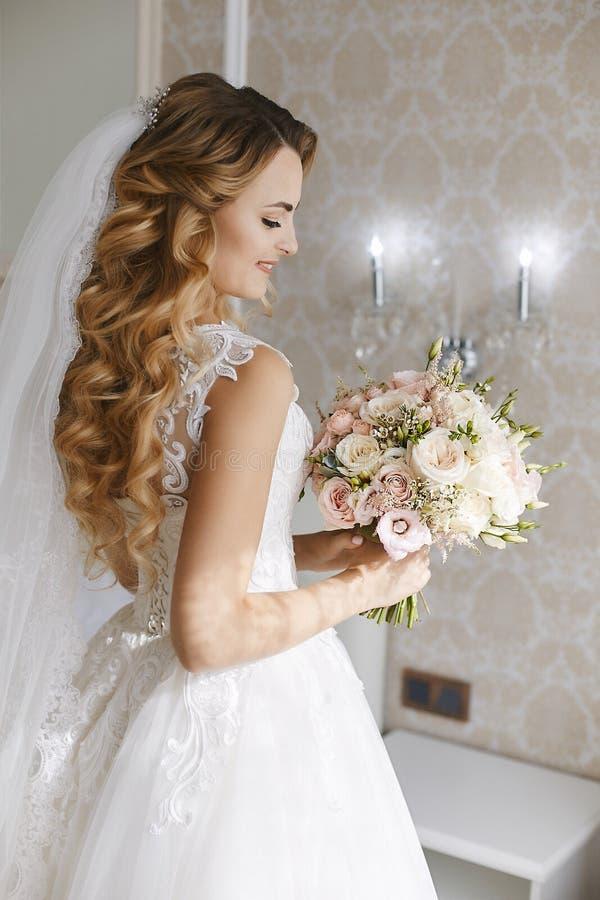 有时髦的婚姻的发型的美丽的年轻白肤金发的新娘在有花束的一件白色时兴的礼服 免版税库存照片