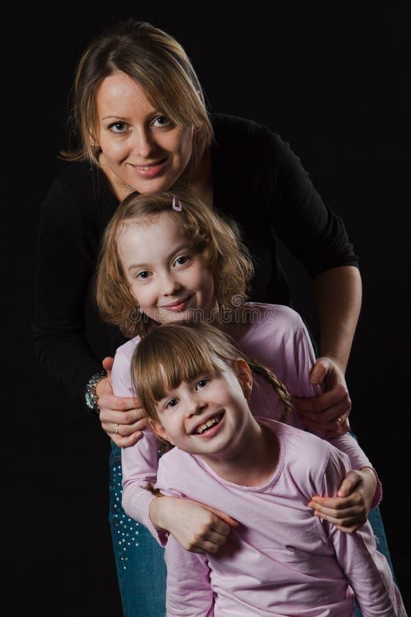 有愉快地摆在两个的女儿的愉快的母亲 免版税库存图片