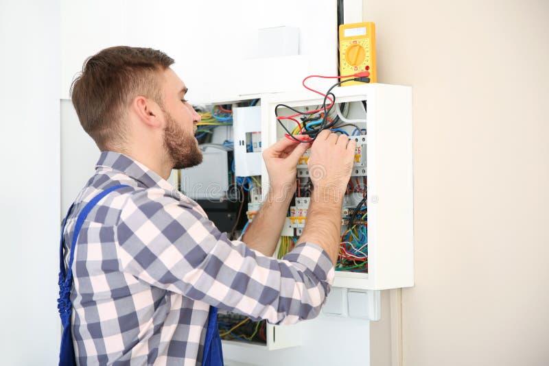 有数字式多用电表的电工检查电压的 库存图片