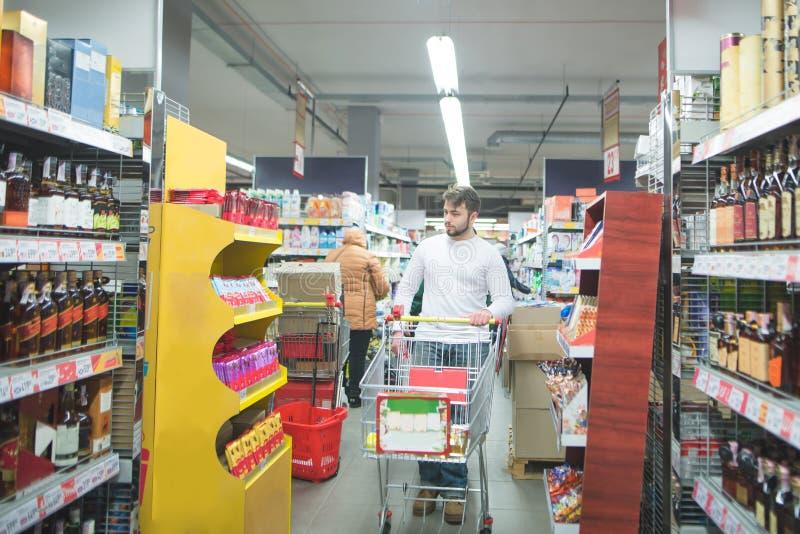 有手推车的人在超级市场的酒精部门走并且选择酒 免版税库存图片