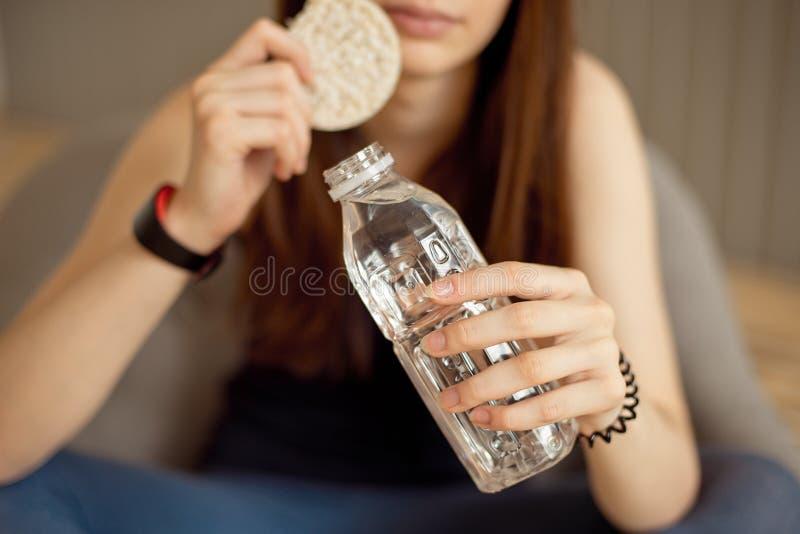 有拿着酥脆年糕和一个瓶净水,健康食品,健康生活方式的黑发的体育女孩 免版税库存照片