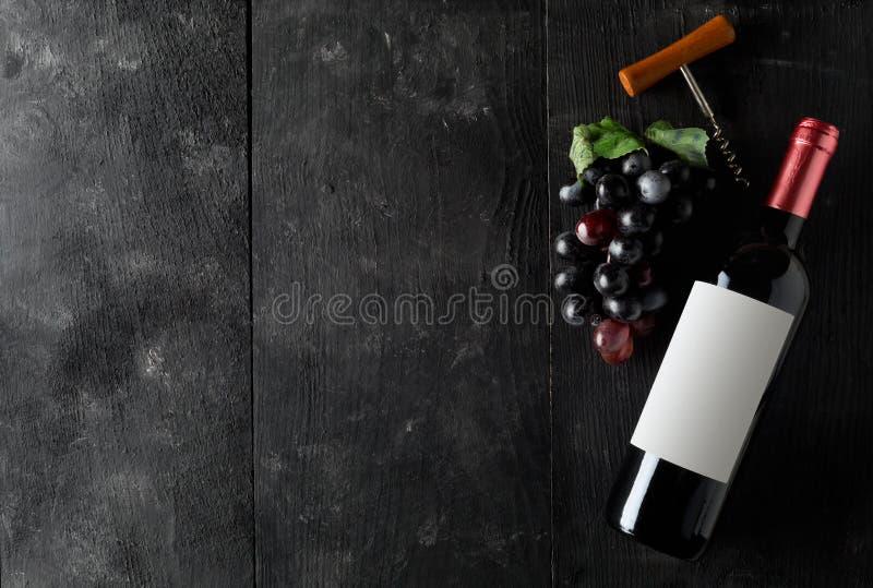 有拔塞螺旋和葡萄的红酒酒瓶在黑暗的木桌平的位置从上面 库存照片
