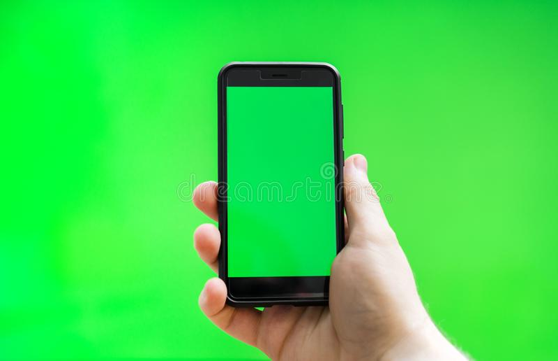 有智能手机的男性手在绿色屏幕 库存照片